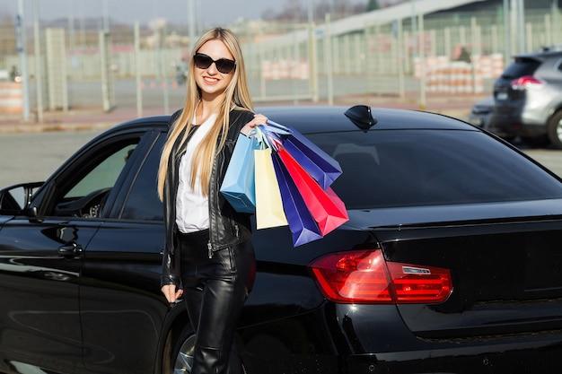 Frau, die farbige taschen nahe ihrem auto hält