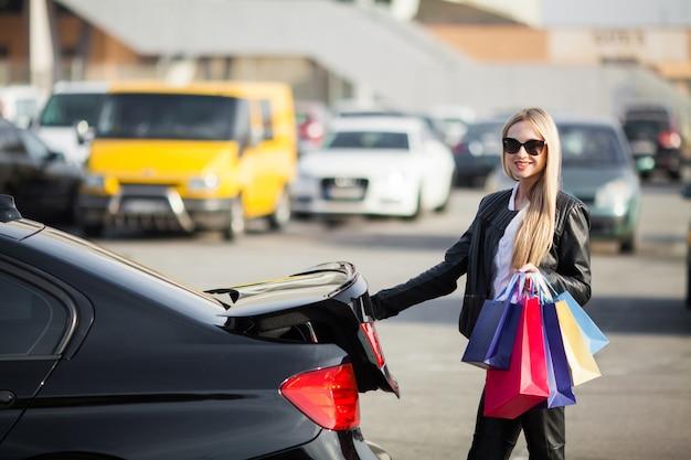 Frau, die farbige taschen nahe ihrem auto im schwarzen freitagurlaub hält.