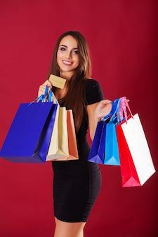 Frau, die farbige taschen und kreditkarte auf roter wand hält