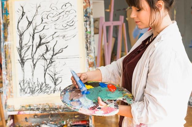 Frau, die farbpalette für das malen an der werkstatt vorbereitet
