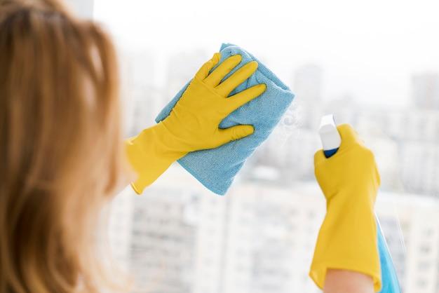 Frau, die fenster mit lappen reinigt