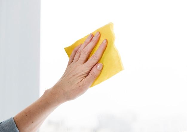 Frau, die fenster sauber wischt