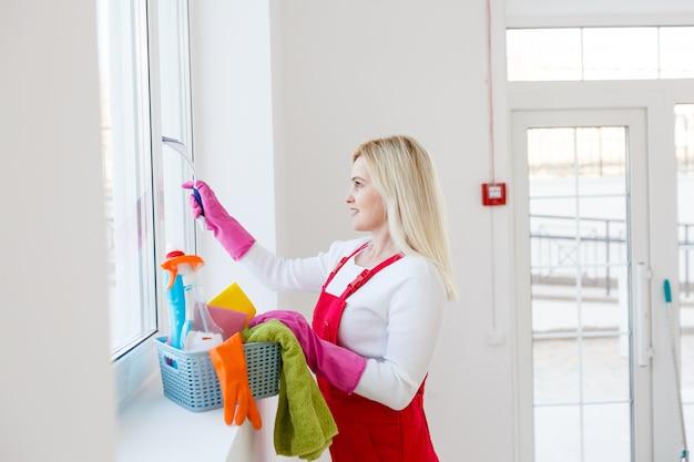 Frau, die fenster zu hause mit reinigungsmitteln reinigt