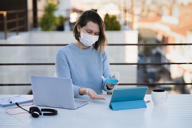 Frau, die fern zu hause terrasse mit laptop und kopfhörern arbeitet