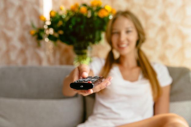 Frau, die fernsehfernsteuerungs- und -surfprogramme im fernsehen hält.
