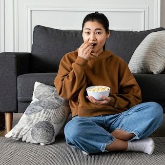Frau, die fernsieht und popcorn isst
