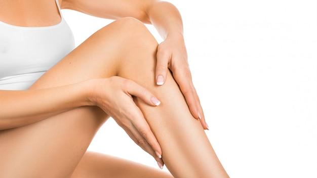 Frau, die feuchtigkeitscreme auf ihren perfekten beinen anwendet, lokalisiert auf weißem hintergrund. haut- und körperpflegekonzept