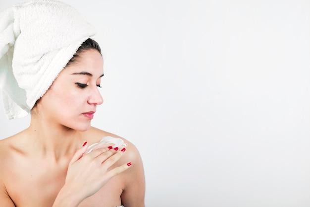 Frau, die feuchtigkeitscreme zu ihrer schulter gegen weißen hintergrund anwendet