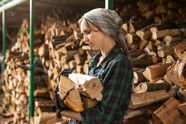 Frau, die feuerholz trägt