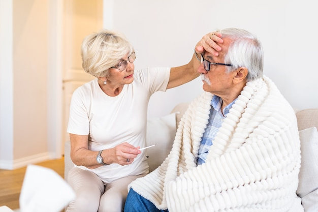 Frau, die fiebertemperatur des älteren mannes prüft