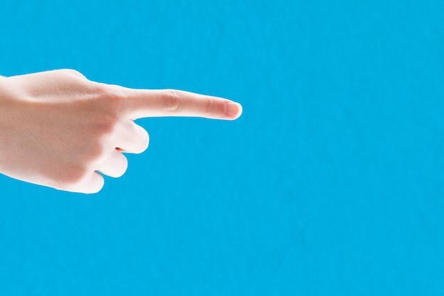 Frau, die finger auf blauem hintergrund zeigt