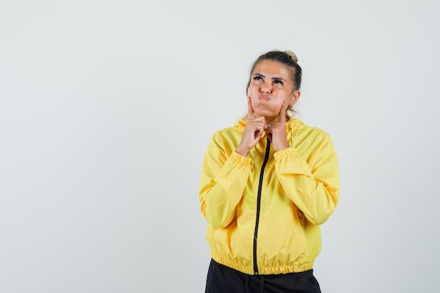 Frau, die finger auf wangen im sportanzug hält und nachdenklich aussieht. vorderansicht.