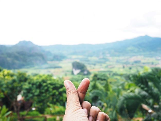 Frau, die finger mini-herzform oder liebe symbolisch von korea über verschwommenem berg zeigt