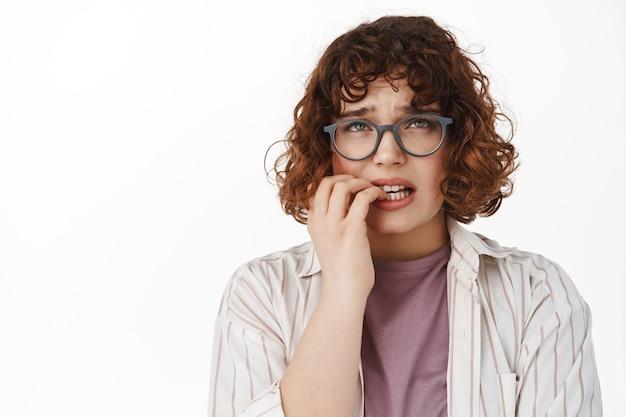 Frau, die fingernägel beißt und nervös aufschaut, sich besorgt fühlt, wenn sie nach oben schaut, in panik gerät, auf weiß steht