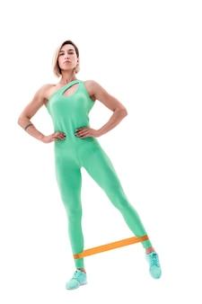 Frau, die fitness-widerstandsbänder im studio lokalisiert auf weiß ausübt