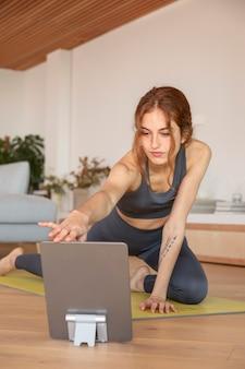 Frau, die fitness zu hause auf matte tut