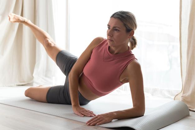 Frau, die fitnessübungen an ihrem haus tut