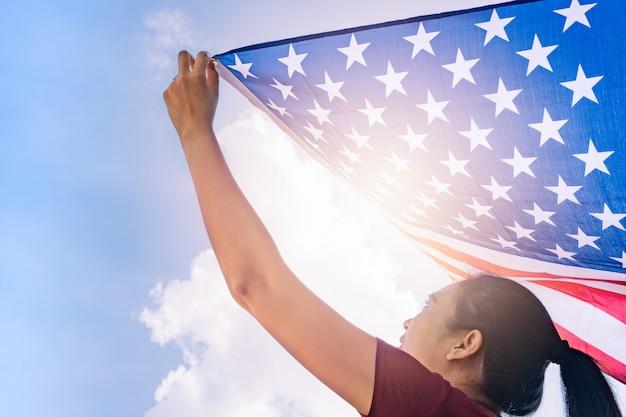 Frau, die flagge der vereinigten staaten von amerika auf sonnigem himmel hält. usa memorial day und independence day konzept.