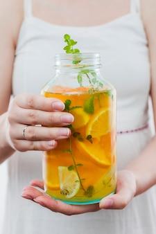 Frau, die flasche des zitrusfruchtgetränks hält