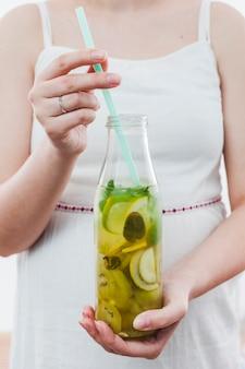 Frau, die flasche grüne limonade hält