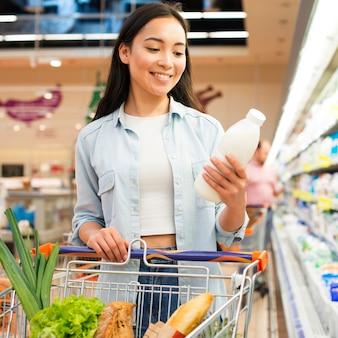 Frau, die flasche milch am gemischtwarenladen kontrolliert