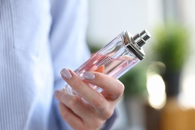 Frau, die flasche parfüm in ihren händen nahaufnahme hält
