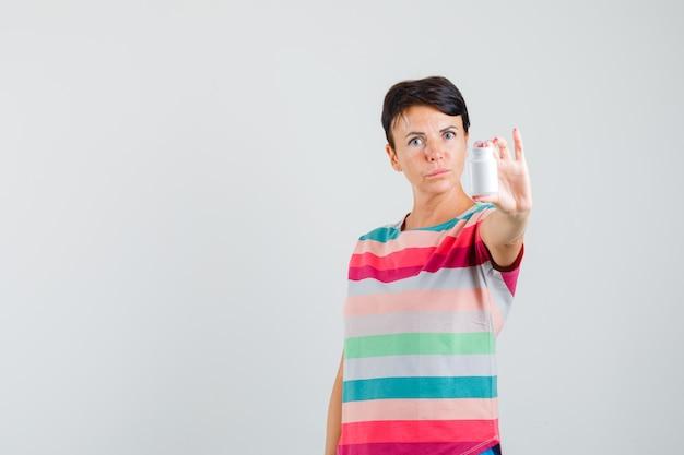 Frau, die flasche pillen im gestreiften t-shirt präsentiert und vorsichtig schaut