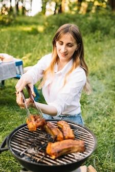 Frau, die fleisch in der natur grillt