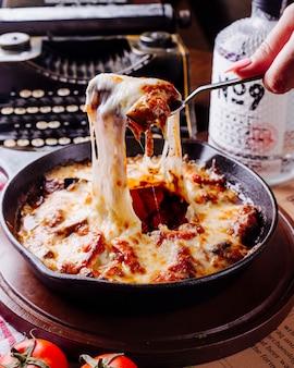 Frau, die fleischeintopf mit käse von einer schwarzen wanne mit tischbesteck nimmt.