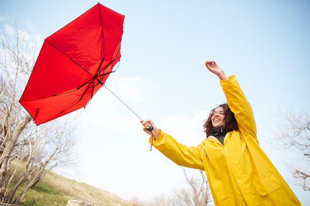 Frau, die fliegenden regenschirm fängt