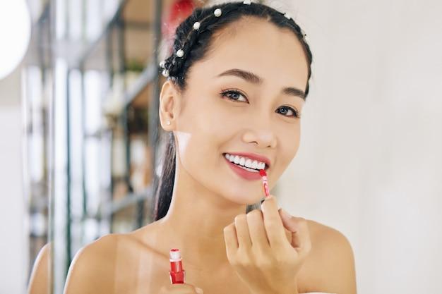 Frau, die flüssigen lippenstift anwendet