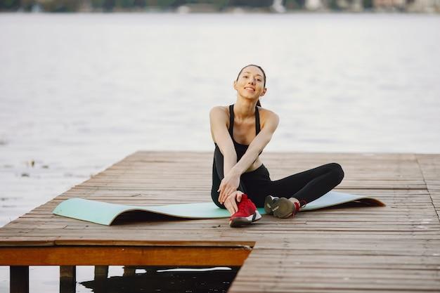 Frau, die fortgeschrittenes yoga am wasser praktiziert