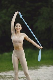 Frau, die fortgeschrittenes yoga an einem sommerstrand praktiziert