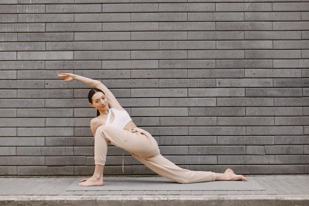 Frau, die fortgeschrittenes yoga gegen eine dunkle stadtmauer praktiziert