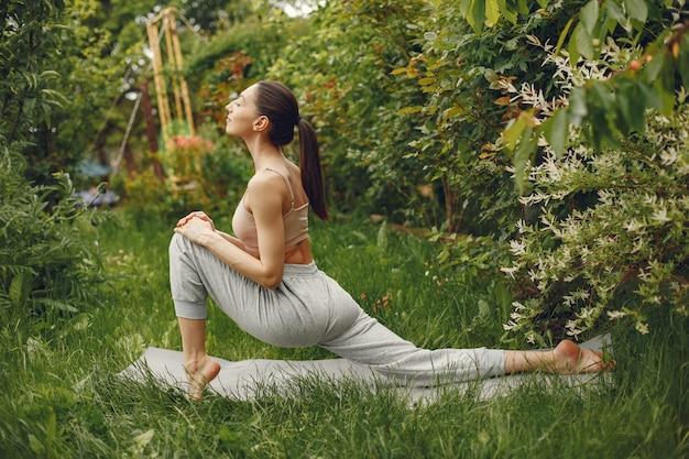 Frau, die fortgeschrittenes yoga in einem park praktiziert