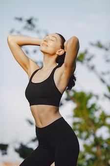 Frau, die fortgeschrittenes yoga in einem sommerpark praktiziert