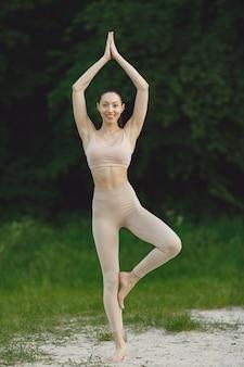 Frau, die fortgeschrittenes yoga in einem strand praktiziert