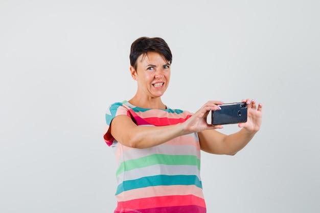 Frau, die foto auf handy in gestreiftem t-shirt nimmt und genervt schaut. vorderansicht.
