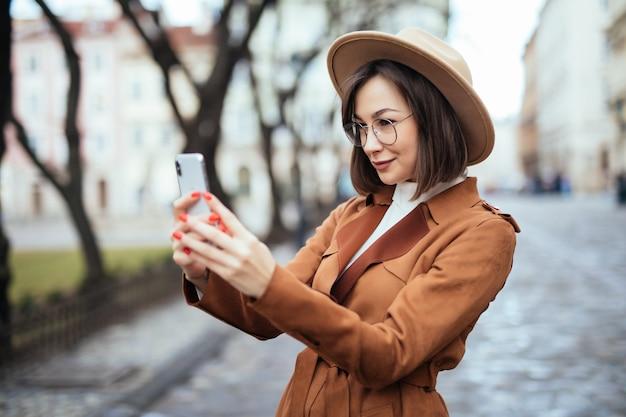 Frau, die foto auf ihrem telefon am herbsttag draußen nimmt