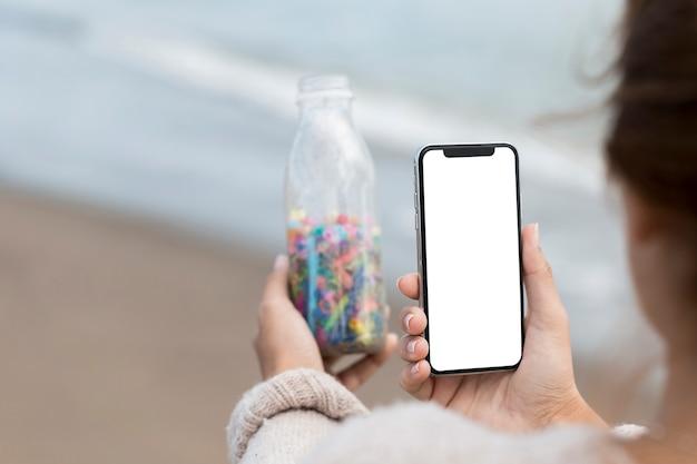 Frau, die foto der flasche mit plastik nimmt