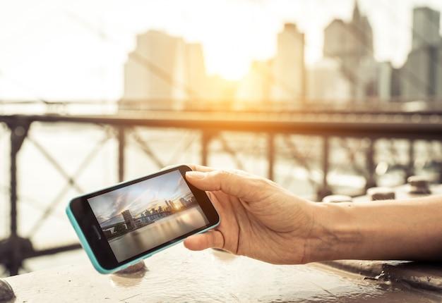 Frau, die foto der skyline von new york city auf dem smartphone beobachtet.