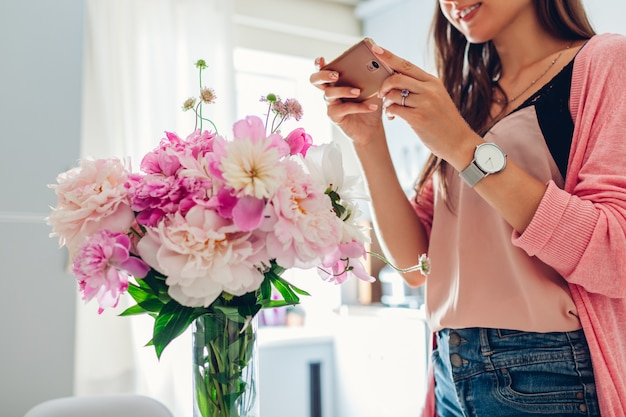 Frau, die foto des blumenstraußes der pfingstrosenblumen nimmt