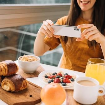 Frau, die foto des frühstücks bei tisch macht