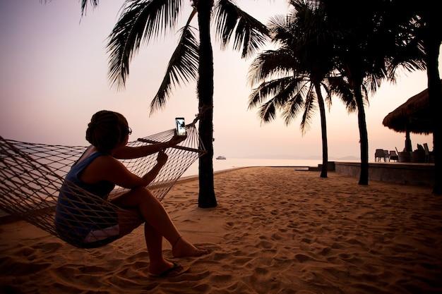 Frau, die foto durch intelligentes telefon an der dämmerung macht