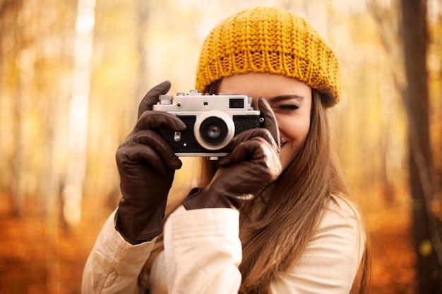 Frau, die foto durch retro-kamera nimmt