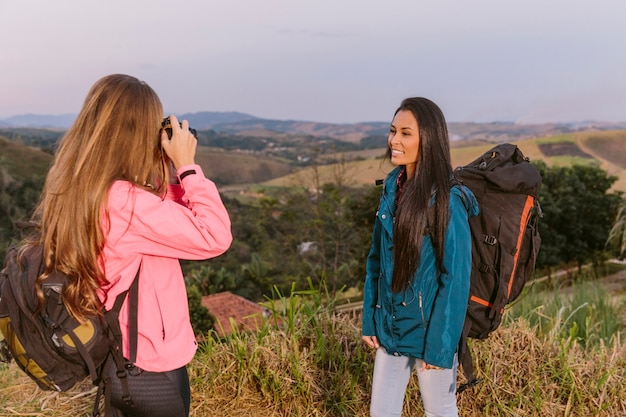 Frau, die foto ihres freundes mit rucksack macht