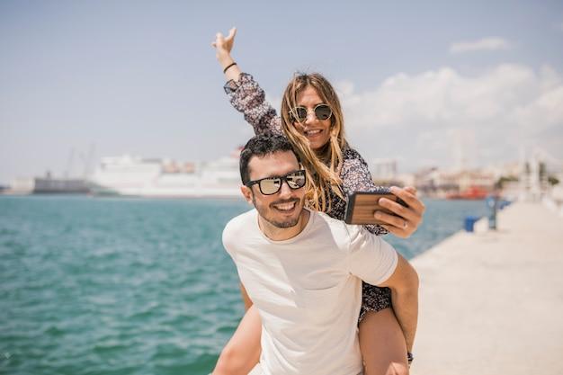 Frau, die foto ihres freundes piggyback fahrt auf seinem zurück genießt macht