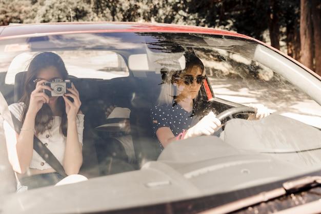 Frau, die foto mit kamera beim reisen mit ihren freunden im auto macht