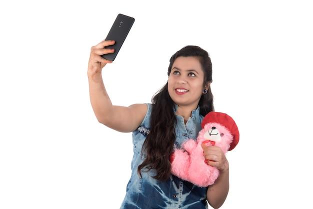 Frau, die foto oder selfie mit handy nimmt und teddybär hält