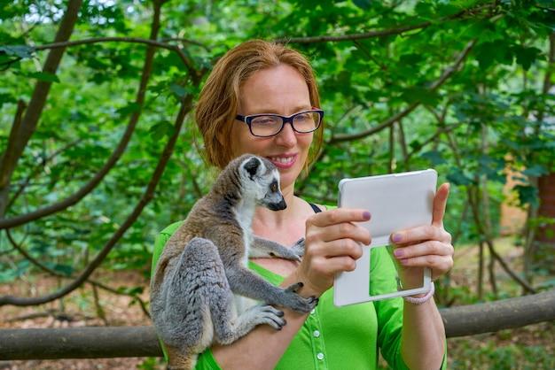 Frau, die foto selfie mit ring angebundenem lemur nimmt